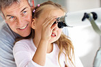 Young girl looking through telescope with father