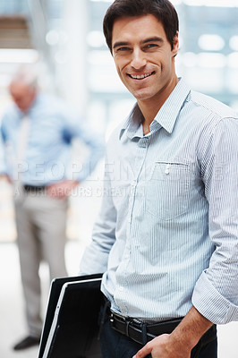 Buy stock photo Friendly young business executive smiling with colleague in the background