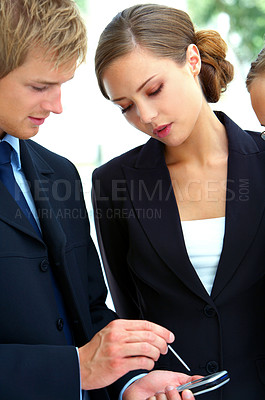 Buy stock photo Cropped shot of three business colleagues looking at a cellphone together