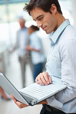 Buy stock photo Happy smart business man using laptop with colleagues in the background
