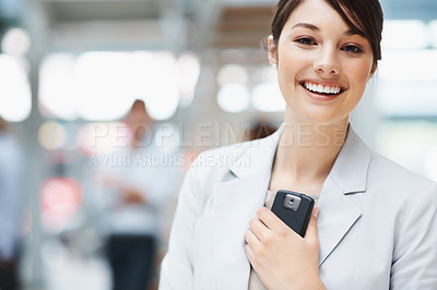Buy stock photo Portrait of a cute smiling business female holding a cell phone on blur background