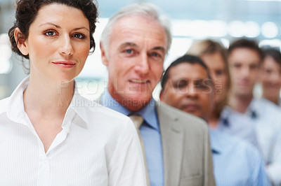 Buy stock photo Portrait of a beautiful mature business woman standing with colleagues in line at the back