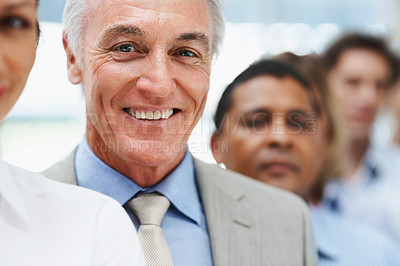 Buy stock photo Closeup of a smiling senior business man standing in line with colleagues