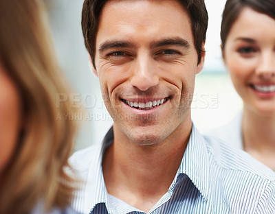Buy stock photo Closeup of a handsome happy business man in line with colleagues