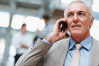Buy stock photo Thoughtful senior business man speaking on cellphone with colleagues at the back