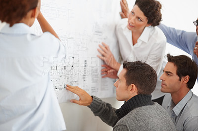 Buy stock photo Group business people studying a production chart displayed on the wall