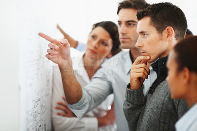 Buy stock photo Group of business associates looking and pointing at a chart put up on the wall