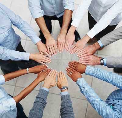 Buy stock photo Top view of a group of business people standing in a circle with their hands together in a sign of unity