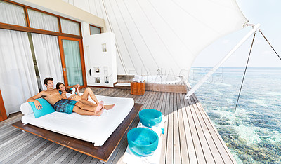 Buy stock photo Attractive young couple lying on a day bed in a resort together and looking over a ocean view