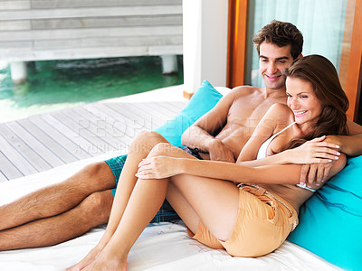 Buy stock photo Happy young couple smiling while sitting together on a day bed