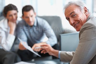 Buy stock photo Smiling mature financial planner with his clients at the back