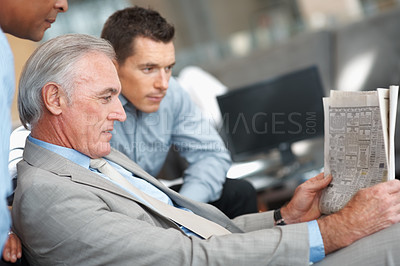 Buy stock photo Profile view of a senior business man reading a newspaper with colleagues