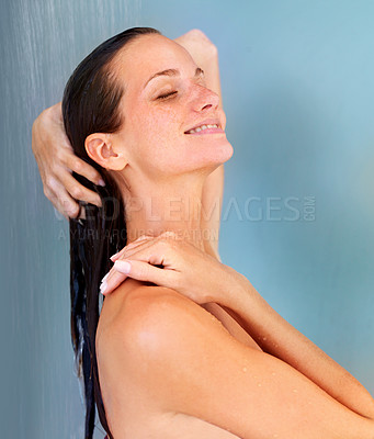 Buy stock photo Gorgeous young woman standing the shower and smiling with her eyes closed as the water runs over her