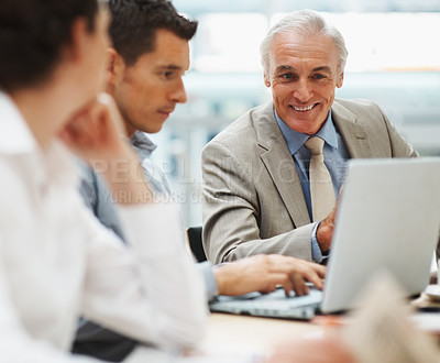 Buy stock photo Happy senior business man with colleagues in a meeting -everyone looking at laptop
