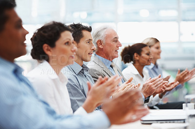 Buy stock photo Multi ethnic coworkers sitting in a line and applauding at conference table