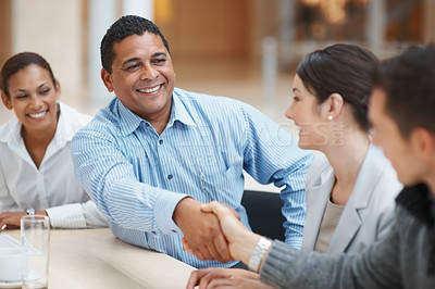 Buy stock photo Mature man handshaking with partner after striking a business deal