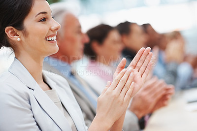 Buy stock photo Pretty young business woman with colleagues applauding at a seminar