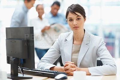 Buy stock photo Confident business woman at desk with colleagues in the background
