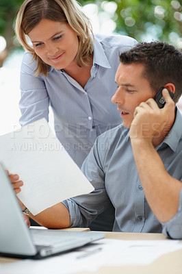Buy stock photo Business man handing a paper to colleague while he speaks on the phone