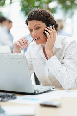 Buy stock photo Mature business woman talking on cellphone while sitting in front of the laptop