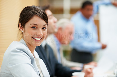 Buy stock photo Cute young business woman smiling at a meeting with colleagues at the back