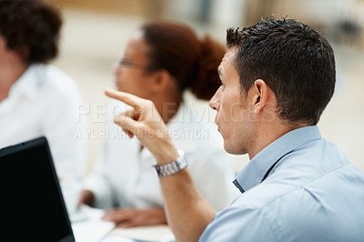 Buy stock photo Young business man at a meeting and pointing at something