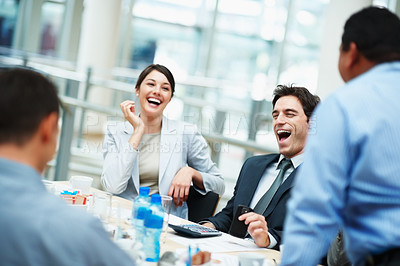 Buy stock photo Business colleagues laughing on a funny joke cracked during the meeting