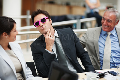 Buy stock photo Funny young business man wearing a pink framed sunglasses at a meeting