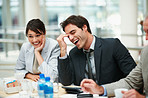 Business colleagues enjoying a laugh at a meeting