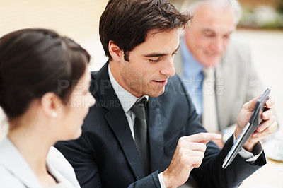 Buy stock photo Handsome business man making calculations using a calculator while at a meeting
