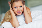Cute woman giving you a warm smile on bed at home