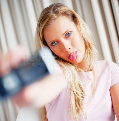 Buy stock photo Pretty young woman making a funny face while photographing herself