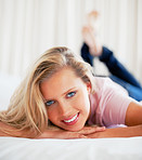 Beautiful smiling female lying on bed at home