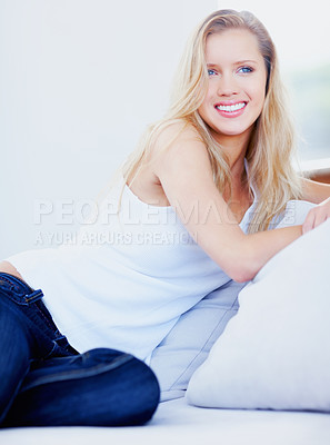 Buy stock photo Portrait of a smiling relaxed young female sitting on a sofa