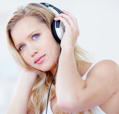 Buy stock photo Cute young woman listening to music through her headphones while looking away dreamily, isolated on white - copyspace