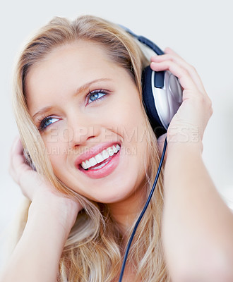 Buy stock photo Closeup of a pretty blond female listening to music over headphones