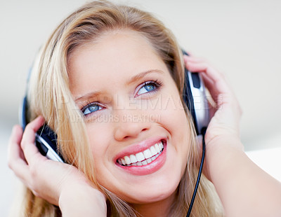 Buy stock photo Closeup portrait of a smiling young woman listening to music over the headphones
