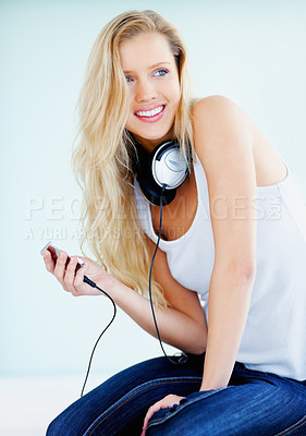 Buy stock photo Modern young blond female holding a music player with the headphones around her neck