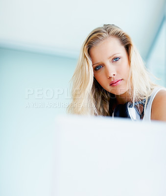Buy stock photo Pretty young blond female with headphones around her neck in front of the laptop