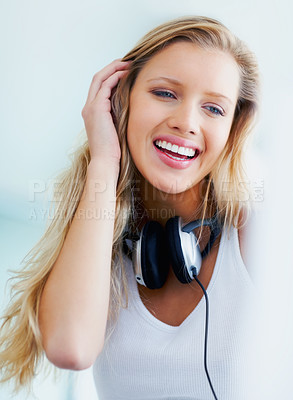Buy stock photo Portrait of a smiling young blond female with headphones around her neck
