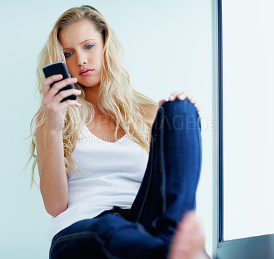 Buy stock photo Beautiful young woman reading a text message by the window