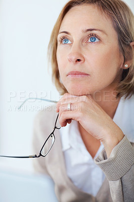 Buy stock photo Portrait of mature woman holding glasses in hand and thinking