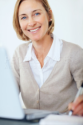 Buy stock photo Closeup portrait of businesswoman taking notes while working on laptop