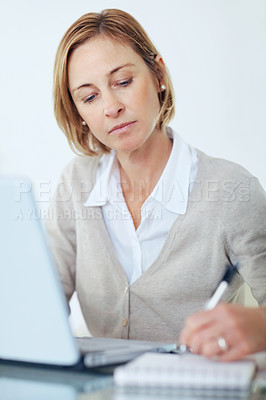 Buy stock photo Portrait of confident middle aged woman using a laptop making a note in notepad
