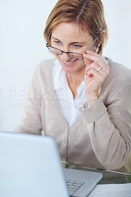 Buy stock photo Portrait of mature business woman working at her desk with a laptop