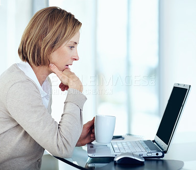 Buy stock photo Portrait of surprised lady looking at laptop holding cup of coffee