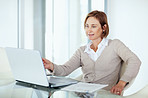 Confident mature businesswoman looking at laptop while at work