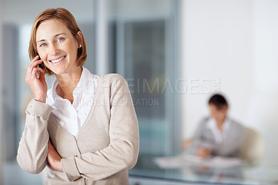 Buy stock photo Portrait of middle aged businesswoman talking on a mobile with a colleague working in background