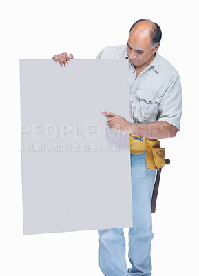 Buy stock photo Portrait of a mature handyman pointing at an empty billboard on white background