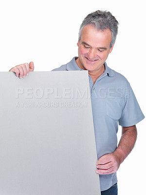 Buy stock photo Portrait of a happy elderly man holding your advertisement on a billboard isolated against white